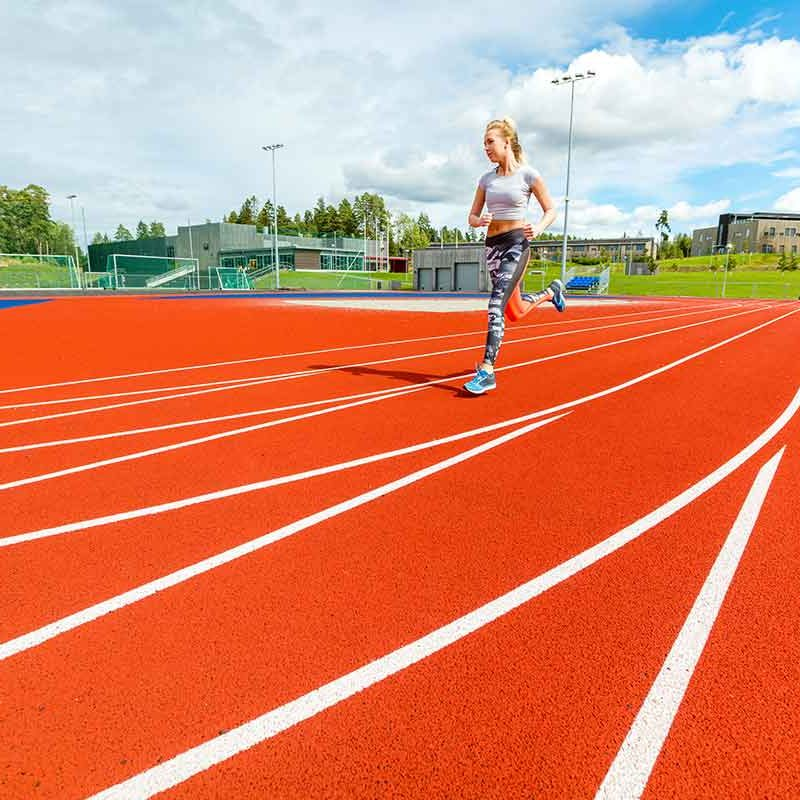 young-woman-running-on-sports-tracks-PNBNHWP